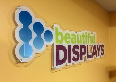 Custom cut acrylic logo sign wall mounted with metal standoffs in the beautifulDISPLAYS office lobby.
